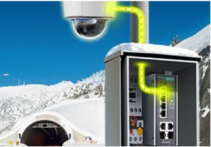 En Ethernetswitch med PoE möjliggör kameraövervakning även på platser långt från strömuttag i väggen, här på bilden visas en enhet som sitter i ett skåp och i bakgrunden synd en tunnelmynning i snölandskap.